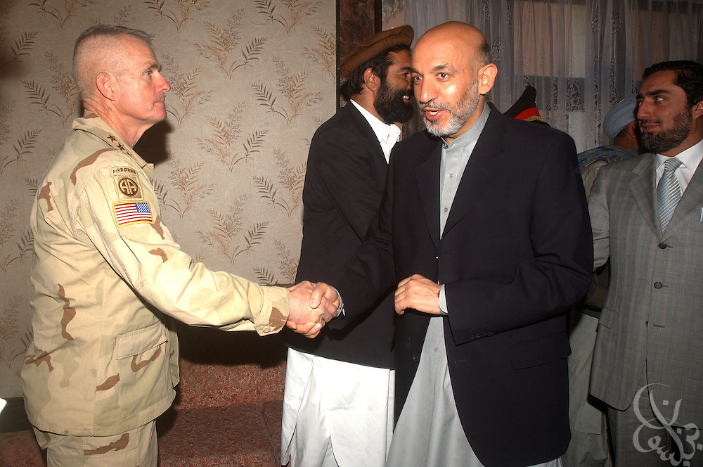 US Army General Dan McNeill, Coalition Joint Task Force 180 commander (left) shakes hands with Afghan president Hamid Karzai as the two gathered for a July 6, 2002 meeting in Kabul regarding a US airstrike that killed innocent civilians last week in the Afghan village of Deh Rawud. McNeill, Karzai and other officials from both sides discussed today's return of two informal boards of inquiry from the site of the bombing and instigated a more formal inquiry to look into the incident.