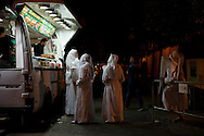 SEVILLE, SPAIN - APRIL 15: Penitents from 'San Gonzalo' brotherhood buy food at a mobile street food van after a 12 hour procession outside their church in the early hours on April 15, 2014 in Seville, Spain. Easter week is traditionally celebrated with processions in most Spanish towns. (Photo by Pablo Blazquez Dominguez/Getty Images)