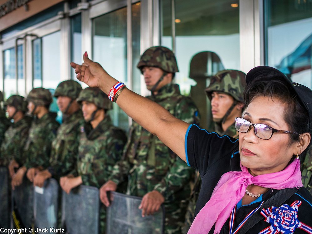 """08 APRIL 2014 - BANGKOK, THAILAND:  An anti-government protestor blocks the entrance to the Thai Ministry of Justice, which was guarded by Thai soldiers. Several hundred anti-government protestors led by Suthep Thaugsuban went to the Ministry of Justice in Bangkok Tuesday. Suthep and the protestors met with representatives of the Ministry of Justice and expressed their belief that Thai politics need to be reformed and that corruption needed to be """"seriously tackled."""" The protestors returned to their main protest site in Lumpini Park in central Bangkok after the meeting.   PHOTO BY JACK KURTZ"""