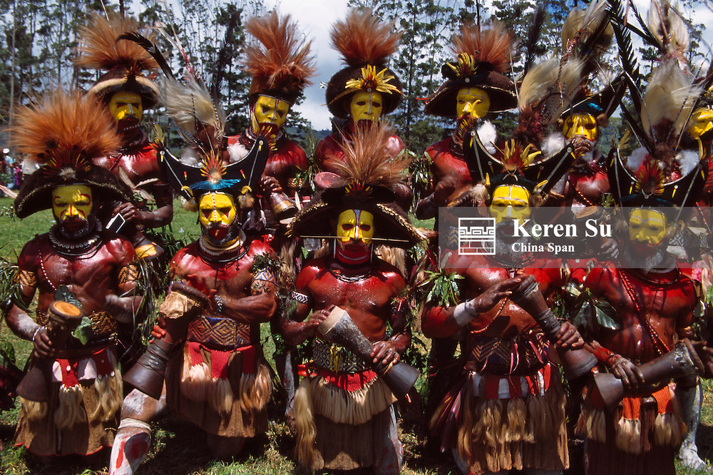 Huli wigmen beating kundu drum and dancing at Sing Sing Festival, Mt. Hagen, Papua New Guinea