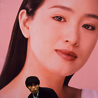 Illegal street trader keeping an eye out for the police, beneath a poster using Chinese actress Gong Li...From China [sur]real © Mark Henley..