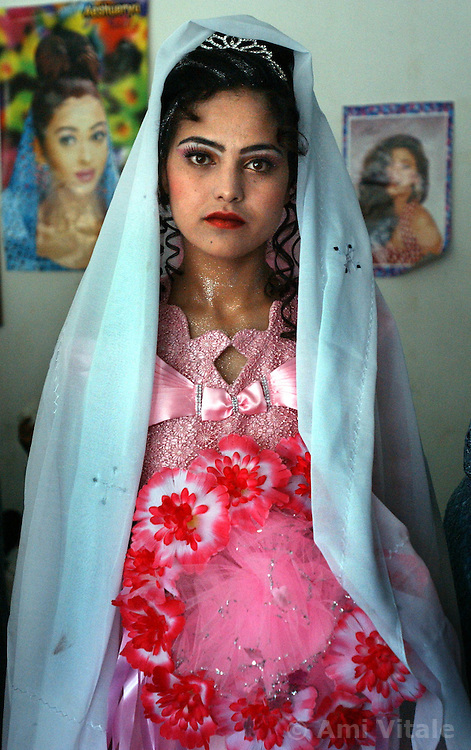 KABUL,AFGHANISTAN - AUGUST 29: An Afghan woman prepares to leave a beauty salon after getting her hair and face made up in preparation for her wedding ceremony, August 30, 2002 in Kabul, Afghanistan. Each Friday, every beauty salon is filled with  brides, the hotels are jammed with young couples and most streets are packed with streams of cars, blaring their horns as Afghans rush to get married after decades of war. (Photo by Ami Vitale/Getty Images)
