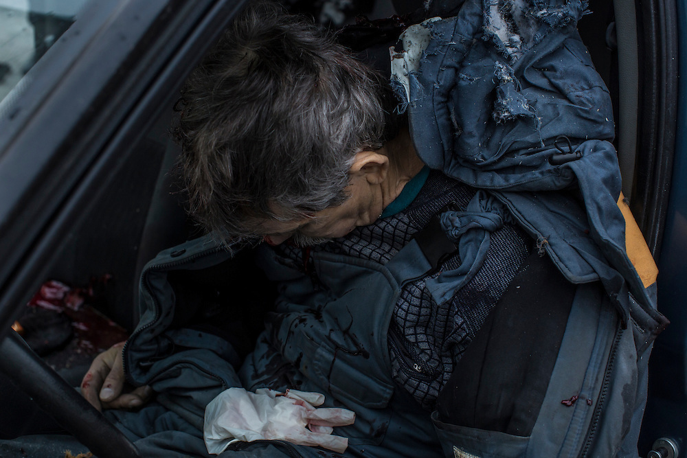 DONETSK, UKRAINE - JANUARY 30, 2015: The body of a man killed by a rocket attack lies in his car in the parking lot of a humanitarian aid distribution center in Donetsk, Ukraine. At least five people were killed at the scene, and at least two others died in a separate shelling nearby. CREDIT: Brendan Hoffman for The New York Times
