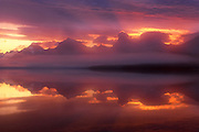 The sunrise colors the storm clouds passing over the mountains along Lake McDonald in Glacier National Park, Montana. Lake McDonald is the largest lake in Glacier National Park, approximately 10 miles (16 km) long, and over a mile (1.6 km) wide. Filling a valley that was carved by glaciers, the lake is 472 feet (130 m) deep.