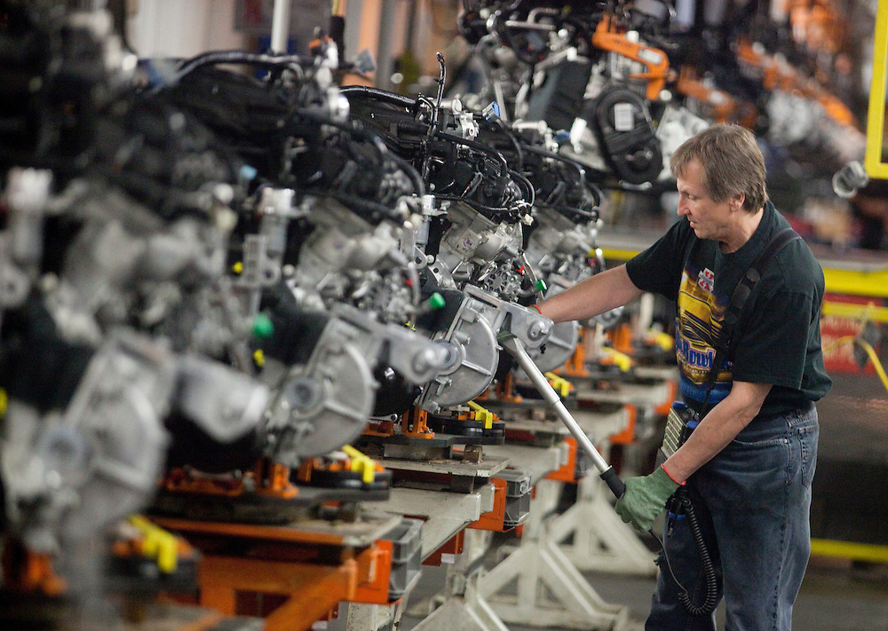 A worker on the production line at Chrysler's plant in Windsor, Ontario, works on the engine for one of the company's new minivans January 18, 2011 as the company celebrated the production launch of the new Dodge Grand Caravan and Chrysler Town and Country.<br /> The Canadian Press/GEOFF ROBINS