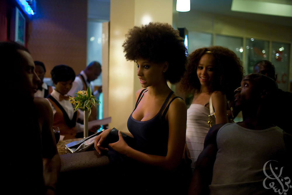 Models Elarica Gallacher(c) Parris Taylor (l) and Rasi Douse (r) kill time in the hotel lobby bar while waiting for a venue power outage to be resolved prior to the July 11, 2008 leg of the THISDAY festival in Abuja, Nigeria. The annual festival is designed to raise awareness of African issues while promoting positive images of Africa using music, fashion and culture in a series of concerts and events in Nigeria, the United States and the United Kingdom. .