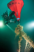 GUE (Global Underwater Explorers) diver guides lift bag as it raises an abandon ghost net from High Seas Wreck of Coronado Island, San Diego, CA