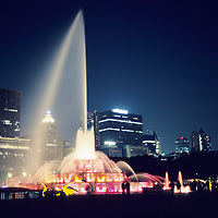 Image of the Chicago Skyline at night with the fountain bein illuminated by colored lights.
