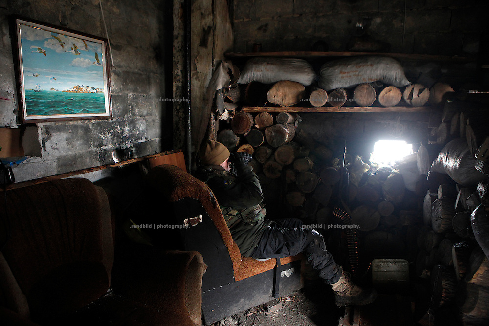 An ukrainian soldier watches the enemy lines through a hole in wall.<br /> <br /> +++   +++ The Boom Stick Brotherhood +++   +++  <br /> <br /> Driven by a certain fascination on military and a simple shaped nationalistic ideology young men travel the world to fight at frontlines of recent conflicts. Five volunteering warriors from europe and the US were walking into battle in Ukraine last year. Ben, Alex, Craig, Charlie and Cowboy made it to the frontline joining the right-wing militia Right Sector (Prawji Sektor) to defend Ukraine by fighting seperatists and russian irregular forces aiming to split off the eastern Donbass region from the country.<br /> <br /> As ukrainian forces are short of servicemen Right Sector is welcomed to support the defense efforts at hotspots. Receiving no payments but shelter, food and ammonition the foreigners selfmade battlegroup Task Force Pluto found itself in a so called Anti-Terror-Operation close to the Donetsk Airport. Though Minsk II Agreement for Ceasefire is in effect several daily fire exchanges taking place between both conflict parties at the line of contact. However the war is now fought in a World War I alike stalemate in muddy trenches which were digged during the World War II.<br /> <br /> As a loose union of individuals the Boom Stick Brotherhood is no certain ukrainian phenomenon and not tied to the recent war only. If things would become boring, crazy or if the army leadership would deter foreigners from fighting Ben and his comrades would move on looking for another destination around the globe to be involved in battle. That&acute;s what they are aiming for. They are living a dream of smoking guns, camaraderie and a simple outdoor life. A lifestyle devoted to look every day into the ugly face of death.<br /> <br /> The Boom Stick Brotherhood is a multi-national, multi-religious and multi-ethnic group of men in its twenties:<br /> Ben, an austrian infantryman travelling to hot zones since years. Bored and frustrated