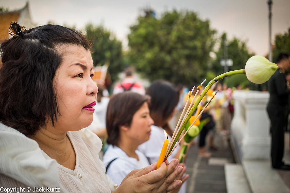 "25 FEBRUARY 2013 - BANGKOK, THAILAND:  Thai Buddhists pray at Wat Benchamabophit Dusitvanaram (popularly known as either Wat Bencha or the Marble Temple) on Makha Bucha Day. Makha Bucha is a Buddhist holiday celebrated in Myanmar (Burma), Thailand, Cambodia and Laos on the full moon day of the third lunar month (February 25 in 2013). The third lunar month is known in Thai is Makha. Bucha is a Thai word meaning ""to venerate"" or ""to honor"". Makha Bucha Day is for the veneration of Buddha and his teachings on the full moon day of the third lunar month. Makha Bucha Day marks the day that 1,250 Arahata spontaneously came to see the Buddha. The Buddha in turn laid down the principles his teachings. In Thailand, this teaching has been dubbed the 'Heart of Buddhism'.     PHOTO BY JACK KURTZ"