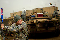 Before heading out on a mission, U.S. Army Spec. Timothy McClellan plays a game of rock-baseball at a remote outpost in Kahn Bani Sahd, Iraq, on Feb. 6, 2007.