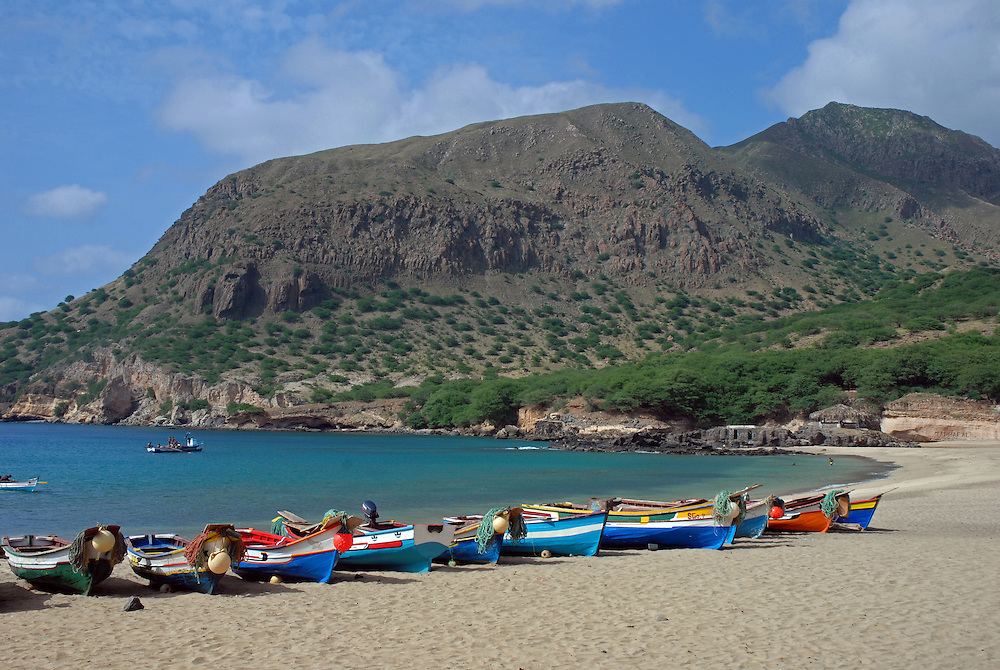 Wooden fishing boats hauled up on to the beach at Tarrafal, Santiago Island, Cape Verde Islands (Capo Verde).  The flat topped Monte Graciosa can be seen in the background.