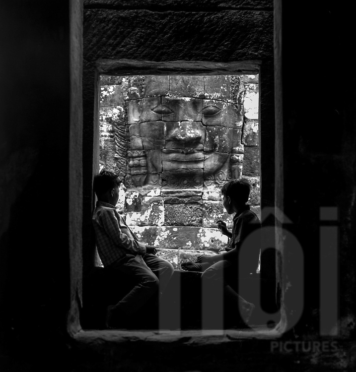 Young Cambodian boys converse in the shadows beside a massive stone face of the Bayon temple, <br /> Angkor, Siem Reap, Cambodia, 2005, Southeast Asia