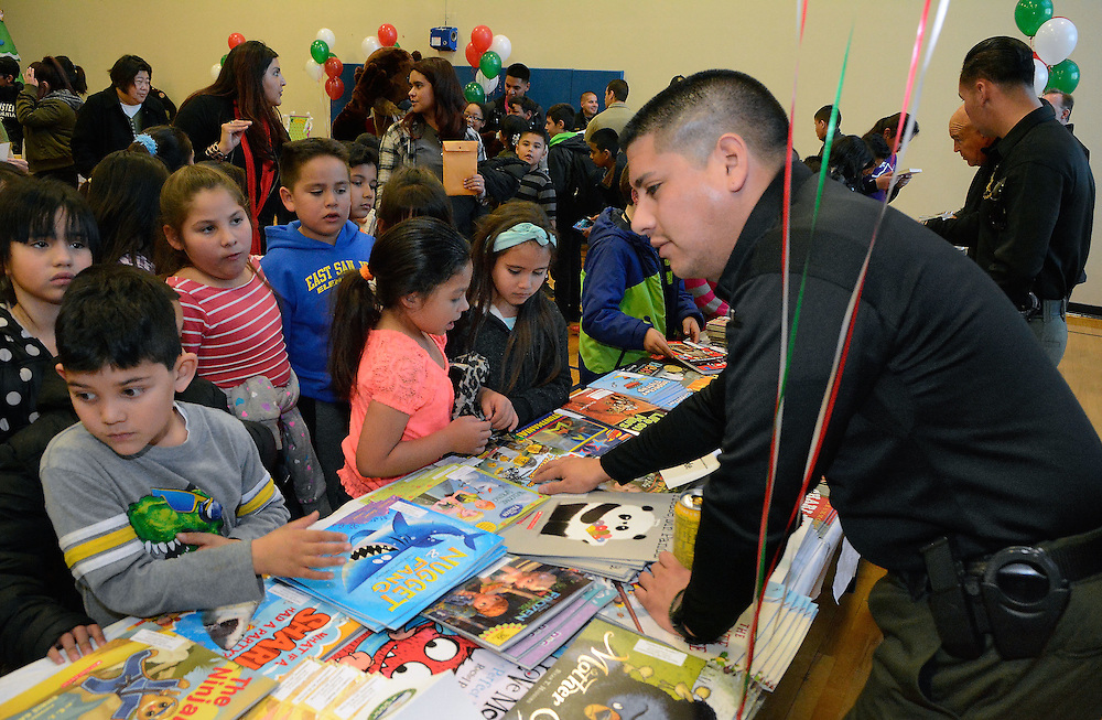 jt120716c/a sec/jim thompson/BCSO officer Mark Cerna tries to help Joisah Montez pick out a book at the Mountain View Community Center during the Children's Book Fiesta. Wednesday Dec. 07, 2016. (Jim Thompson/Albuquerque Journal)