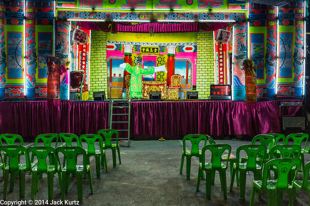 """25 JANUARY 2014 - BANG LUANG, NAKHON PATHOM, THAILAND: A Chinese opera performance in a small town near Bang Luang, Nakhon Pathom, Thailand. Chinese opera was once very popular in Thailand, where it is called """"Ngiew."""" It is usually performed in the Teochew language. Millions of Chinese emigrated to Thailand (then Siam) in the 18th and 19th centuries and brought their cultural practices with them. Recently the popularity of ngiew has faded as people turn to performances of opera on DVD or movies. There are still as many 30 Chinese opera troupes left in Bangkok and its environs. They are especially busy during Chinese New Year when travel from Chinese temple to Chinese temple performing on stages they put up in streets near the temple, sometimes sleeping on hammocks they sling under their stage.     PHOTO BY JACK KURTZ"""