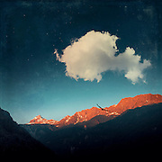 Big cloud over a illuminated alpine mountain range - manipulated photograph