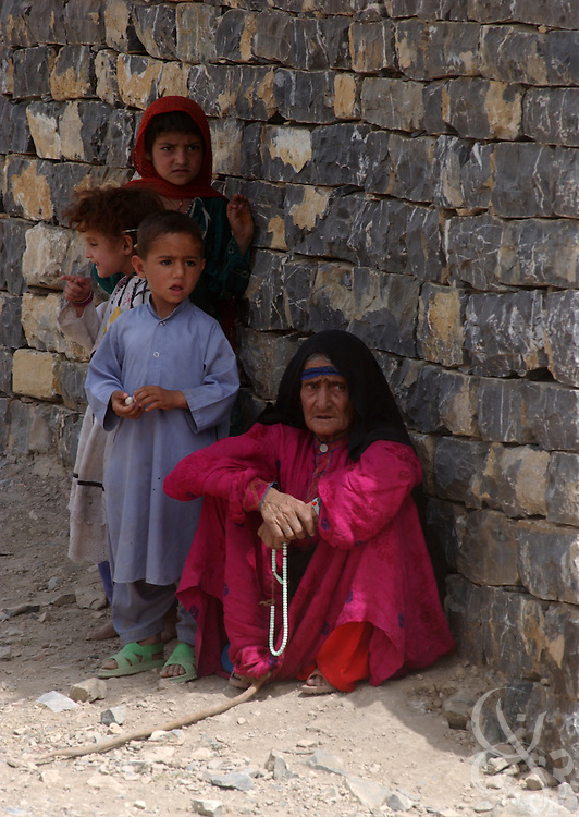 An Afghan woman and her family watch as fellow villagers are given  free medical care during a joint US-UK military humanitarian mission June 18, 2002 at a remote village in southeastern Afghanistan.