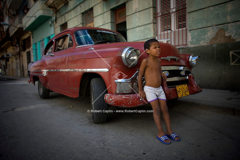 cuban boy leaning on vintage red chevy
