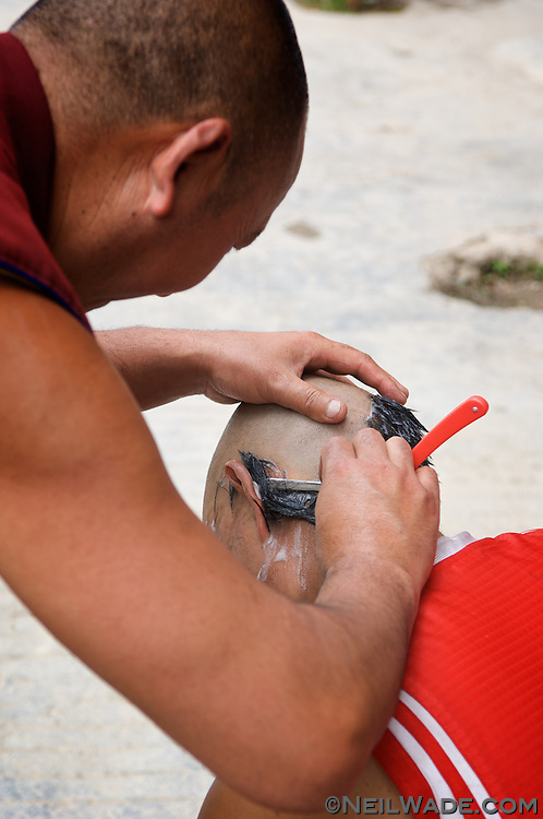 Tibetan Buddhist monks take turns shaving each other's heads in Ganze, Tibet (China).