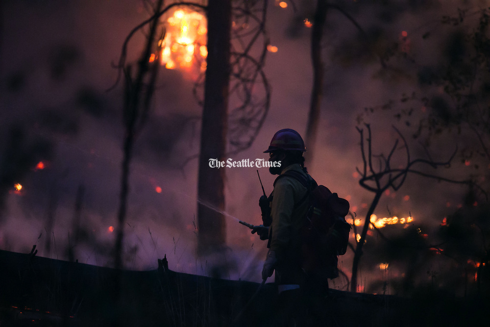 A wildland firefighter works on a blaze in Conconull on Friday August 21, 2015.<br /> <br /> Bettina Hansen / The Seattle Times