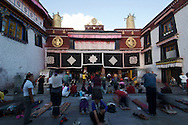 Tibetan pilgrims worship in front of the Jokhang by prostrating themselves repeatedly.