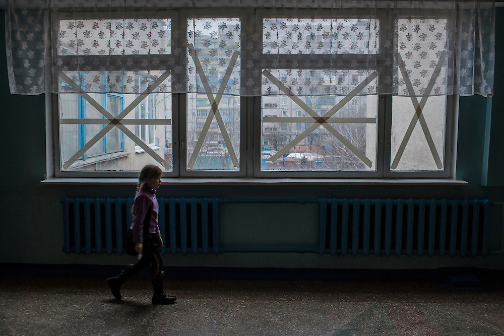 MARIUPOL, UKRAINE - FEBRUARY 6, 2015: A student at School 68 walks past windows taped to secure the glass in case of shelling in Mariupol, Ukraine. On January 24, shelling just nearby killed 31 people and injured over 100, prompting the school to increase the frequency of the drills to daily instead of weekly. CREDIT: Brendan Hoffman for The New York Times