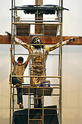 Jeremy Wolf, a sculptor for Inspired Artisans in Milwaukee, climbs down a scaffolding after erecting the corpus of Jesus on a cross in the newly renovated St. Anthony Church in Menomonee Falls. The corpus is made of fiberglass with a bronze finish, stands 10 feet high and weighs about 130 pounds. (Photo by Sam Lucero)