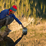 ID00338-00...IDAHO - Backpacker dipping a pan into Alpine Lake in the early morning in the Sawtooth Wilderness Area.