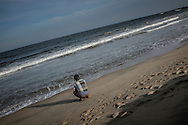 Artisanal fisherman defecates openly on Serenity Beach close to where people are bathing in the surf increasing the change of disease.  Still far more raw sewage finds its way into the sea from various rivers mouths in the city.  Pondicherry, India.