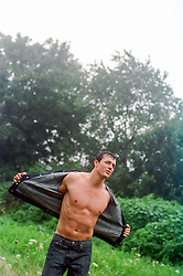 shirtless man in a denim jacket enjoying the rain and air on his body
