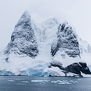 """Nicknamed """"Kodak Gap"""" for its spectacular peaks above a narrow passage, Lemaire Channel lies off of Antarctica, between Kiev Peninsula in the continent's Graham Land and Booth Island. Steep cliffs hem in the iceberg-filled strait, which is 11 km long and narrows to just 1600 meters wide. Lemaire Channel was first seen by the German expedition of 1873-74, but not traversed until December 1898, when the Belgica of the de Gerlache expedition passed through. De Gerlache named it for Charles Lemaire (1863-1925), a Belgian explorer of the Congo. Popular Antarctic cruises are now attracted to Lemaire Channel by protected waters that are often as still as a lake (a rarity in the storm-wracked Southern Ocean), and the north-south traverse delivers vessels close to Petermann Island, home of the world's southernmost colony of Gentoo Penguins. The principal difficulty is that icebergs may fill the channel, especially in early season, obliging a ship to backtrack around the outside of Booth Island to reach Petermann."""