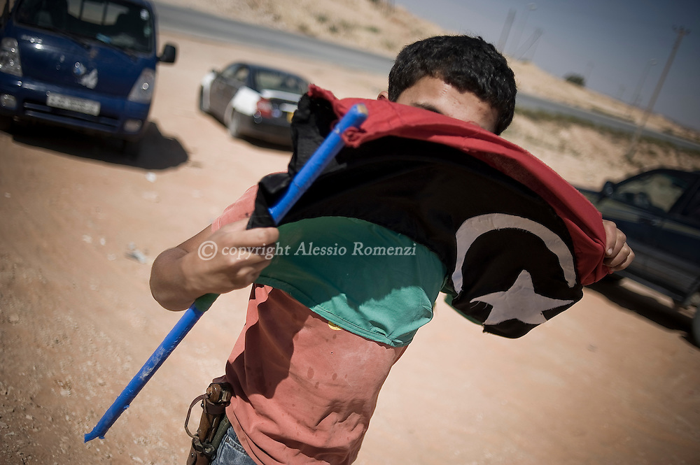 LIBYAN ARAB JAMAHIRIYA, Gualish : A Libyan rebel waves the Libyan flag at the front line on the eastern ridge of the Nafusah Mountains in Western Libya, on the outskirt of Gualish, on July 10, 2011 as forces loyal to Libyan leader Moamer Kadhafi launched a counter attack against rebel advance positions nearby. ALESSIO ROMENZI