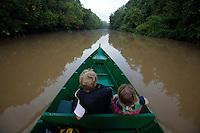Kids ride in a boat up the Menangul River, Borneo.