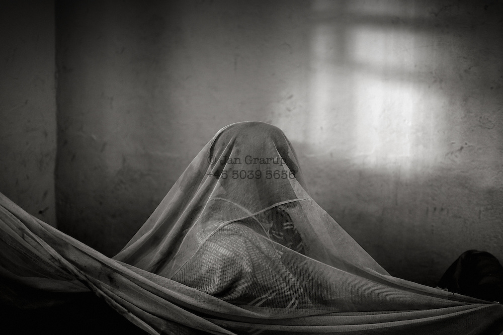 Mogadishu - Somalia 2012 - A patient receiving treatment for his mental disorder at Dr. Habeb's clinic hides under the mosquito net.
