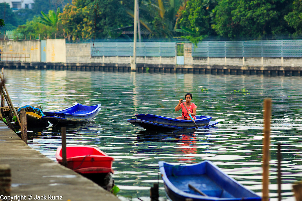 04 JANUARY 2012 - BANGKOK, THAILAND:  A woman paddles her boat on Khlong Phra Khanong near Wat Mahabut. The temple was built in 1762 and predates the founding of the city of Bangkok. Just a few minutes from downtown Bangkok, the neighborhoods around Wat Mahabut are interlaced with canals and still resemble the Bangkok of 60 years ago. Wat Mahabut is a large temple off Sukhumvit Soi 77. The temple is the site of many shrines to Thai ghosts. Many fortune tellers also work on the temple's grounds.   PHOTO BY JACK KURTZ