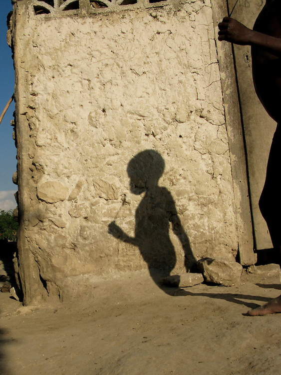 A boy's shadow on the front of his home.