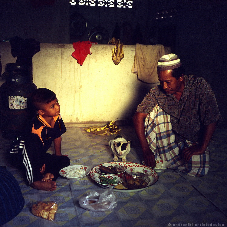 Father and son having breakfast in their house in Karbi village, a small mushlim village near the border with Malaysia. The main production of the village is rubber.