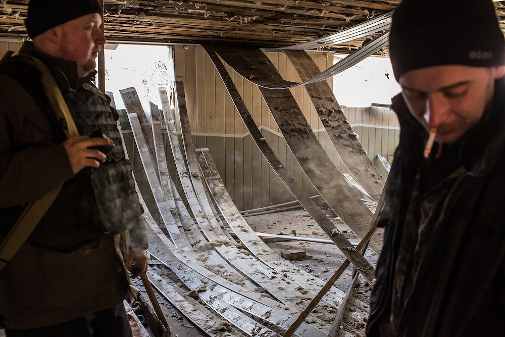 DEBALTSEVE, UKRAINE - FEBRUARY 8, 2015: Ukrainian soldiers show the damage in a building that was hit by shelling earlier in the day in Debaltseve, Ukraine. Fighting between pro-Russia rebels and Ukrainian forces there over the past two weeks has dealt steady casualties to Ukrainian fighters and civilians. CREDIT: Brendan Hoffman for The New York Times