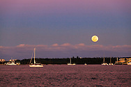 A sailboat cruises through Miami harbor towards the Port of Miami, as the full moon rises over Virginia Key in the background.<br /> WATERMARKS WILL NOT APPEAR ON PRINTS OR LICENSED IMAGES.