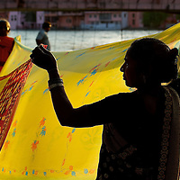 Two women spread a saree in the morning sun to let it dry.