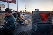 """Activist """"Bosch"""" after lightning a fire in a barrel at the barricades blockading a building supplies store named """"Epicenter"""" in the city of Lviv, Ukraine."""