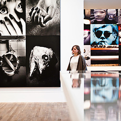 London, UK - 8 October 2012: a woman walks by pictures by Daido Moriyama. The exhibition examine the relationship between the work of William Klein (b.1928) and that of Daido Moriyama (b.1938). Taking as its central theme the cities of New York and Tokyo, the show explores both artists' celebrated depictions of modern urban life.