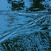 The rough texture of the ice on a frozen pond catches reflections of dark green trees in Snohomish County, Washington.