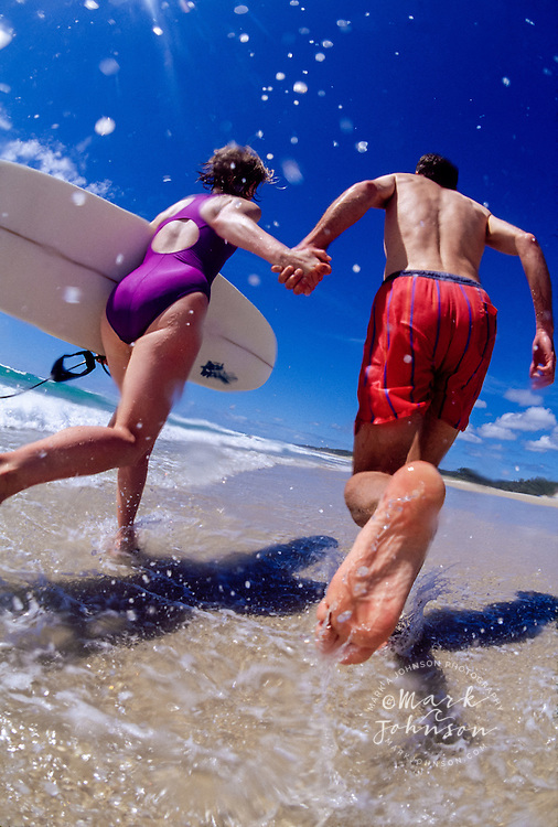 Running couple with a surfboard - Queensland, Australia