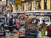 """In Thamel, the bustling tourist center of Kathmandu, Nepal, bicycle driven rickshaws compete with motorcar taxis for passengers, while dodging a crush of motorcycles and pedestrians on narrow streets. Kathmandu, the largest city in Nepal (700,000 people), is sometimes called """"Kantipur"""". The city stands at an elevation of 6235 feet / 2230 meters."""