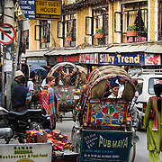 "In Thamel, the bustling tourist center of Kathmandu, Nepal, bicycle driven rickshaws compete with motorcar taxis for passengers, while dodging a crush of motorcycles and pedestrians on narrow streets. Kathmandu, the largest city in Nepal (700,000 people), is sometimes called ""Kantipur"". The city stands at an elevation of 6235 feet / 2230 meters."
