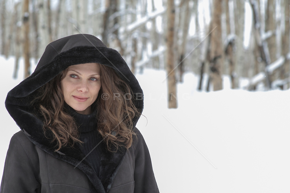 woman with a hooded coat in the snow