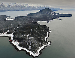 The dark intertidal zone is contrasted against snow along the beaches in this aerial photo of the Chilkat Peninsula near Haines, Alaska after a snow storm. Pictured at lower left is the Letnikof Cove Cannery in this view looking south, down the Chilkat and Chilkoot Inlets towards the Lynn Canal. In the background are the mountains of the Kakuhan Range. The small snow covered bay at upper left is known locally as Mud Bay.