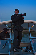 Portrait of Photographer Evan Joseph shooting at dusk in the Long Island Sound, by Heather Prisco.