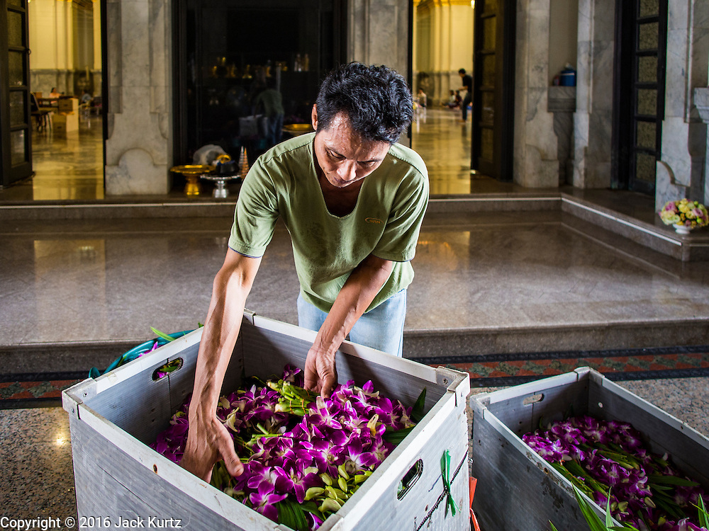 14 JANUARY 2016 - CHACHOENGSAO, CHACHOENGSAO, THAILAND: A worker delivers flowers used in religious rituals to Wat Sothon. Wat Sothon, in Chachoengsao, is one of the largest Buddhist temples in Thailand. Thousands of people come to the temple every day to pray for good luck, they make merit by donating cooked eggs and cash to the temple. The temple dates from the Ayutthaya period (circa 18th century CE).         PHOTO BY JACK KURTZ